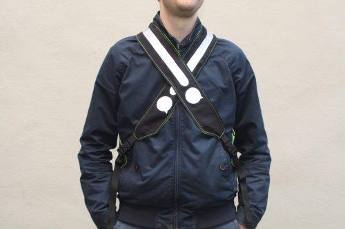 Un homme porte un gilet noir avec des bretelles croisées