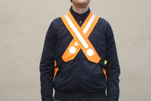 Un homme porte un gilet orange avec des bretelles croisées