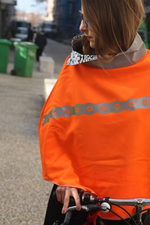 Une femme roule avec un poncho orange VasiMimile