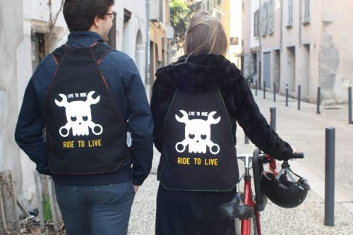 Un couple porte des gilets noir qui lisent Ride to Live