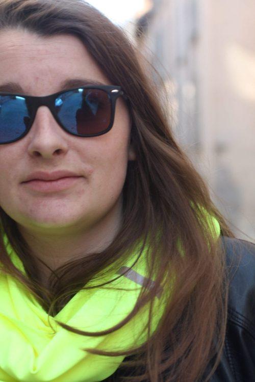 Une femme porte une écharpe fluorescent jaune