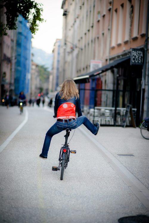 Une femme roule en vélo sans pieds sur les pédales avec une ceinture corsetto rose Vasimimile