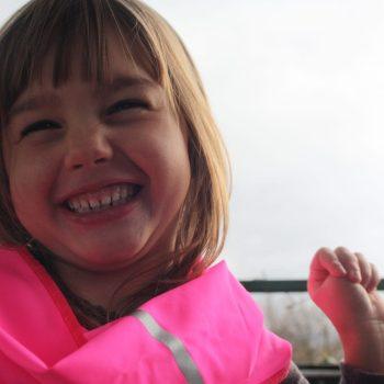 Une fille souriante porte un tour de cou rose