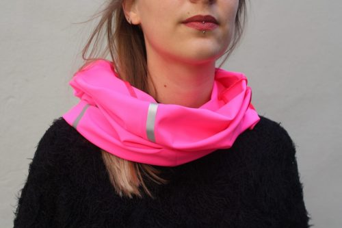 Une femme porte un foulard fluorescent rose