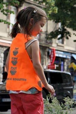 Une jeune fille porte un gilet orange avec des hiboux décoratifs