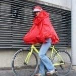 Une personne qui porte un poncho rouge marche avec un vélo jaune