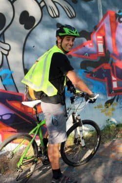 Un homme sur un vélo porte un gilet jaune en souriant