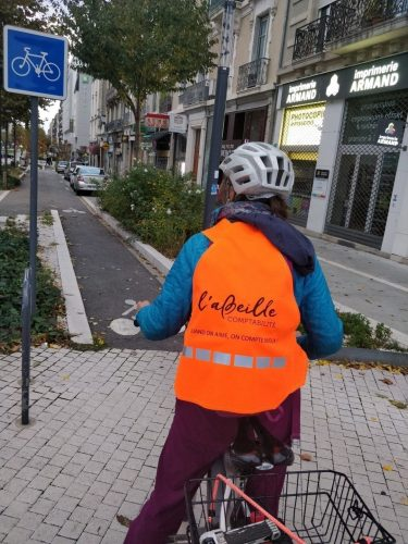 Une femme roule en vélo avec un gilet orange personnalisé