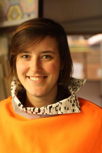 Une photo d'une femme souriante qui porte un poncho orange