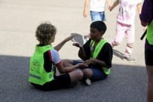 Deux petit garçons jouent en portant des gilet jaunes