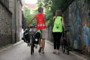 Deux femmes portent des gilets rouge et jaune, elles marchent avec des vélos