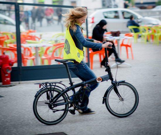 Une femme roule avec un vélo pliable an portant un gilet jaune